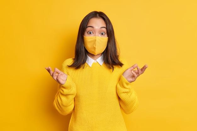 Verwarde aziatische vrouw draagt beschermend masker spreidt handpalmen en kijkt aarzelend weet niet hoe ze een virusepidemie moet stoppen.