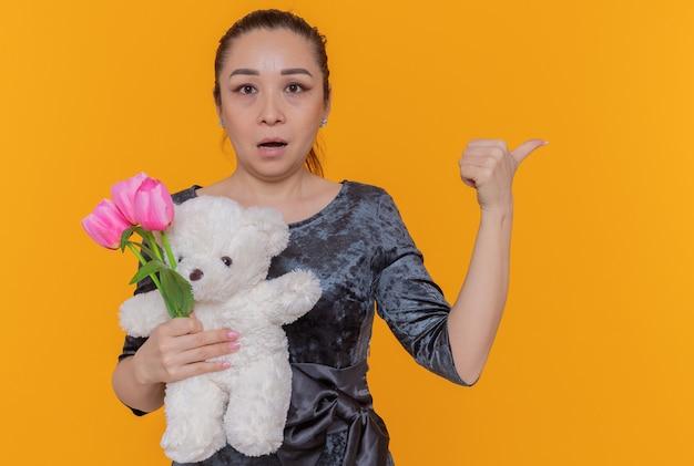 Verwarde aziatische vrouw met boeket van roze tulpen en teddybeer kijkend naar voorkant wijzend met duim ter viering van internationale vrouwendag staande over oranje muur