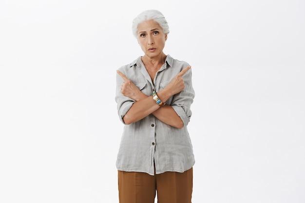 Verwarde besluiteloze oma die met de vingers opzij wijst en hulp vraagt bij de keuze