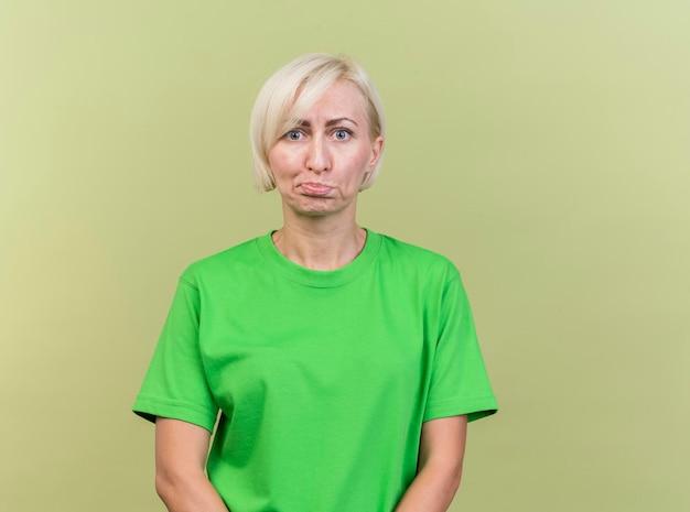 Verwarde blonde slavische vrouw op middelbare leeftijd die voorzijde bekijkt die op olijfgroene muur met exemplaarruimte wordt geïsoleerd