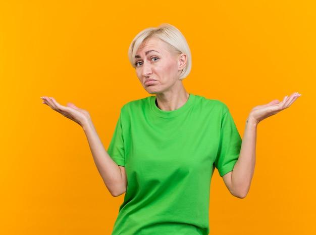 Verwarde blonde vrouw die van middelbare leeftijd naar voorzijde kijkt die ik weet niet gebaar dat op gele muur wordt geïsoleerd
