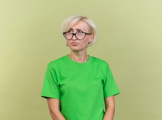 Verwarde blonde vrouw op middelbare leeftijd die glazen draagt die kant bekijken die op olijfgroene muur wordt geïsoleerd Gratis Foto