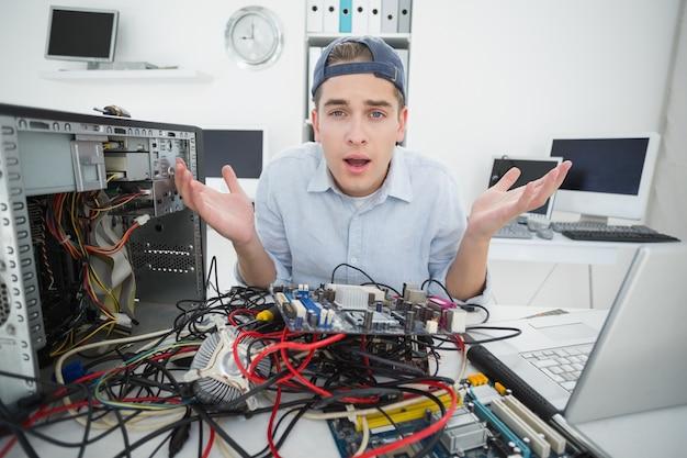 Verwarde computeringenieur die aan gebroken console met laptop werken
