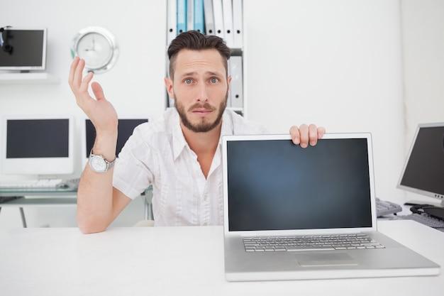 Verwarde computeringenieur die camera met laptop bekijken