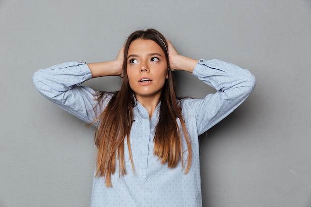 Verwarde donkerbruine vrouw in overhemd dat haar oren behandelt