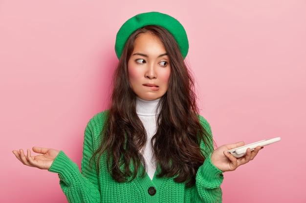 Verwarde donkerharige tiener met aziatische uitstraling, houdt mobiele telefoon vast, spreidt zijn handen zijwaarts, bijt verwarrend op de onderlip, begrijpt niet hoe downloadtoepassing, draagt groene kleding