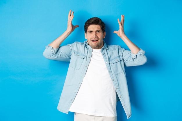 Verwarde en gehinderde man die handen vasthoudt in de buurt van het hoofd, gefrustreerd kijkt, boos staat tegen een blauwe achtergrond