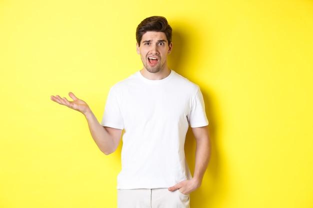 Verwarde en geschokte man die klaagt, één hand opsteekt en er gehinderd uitziet, staande in de buurt van gele kopieerruimte