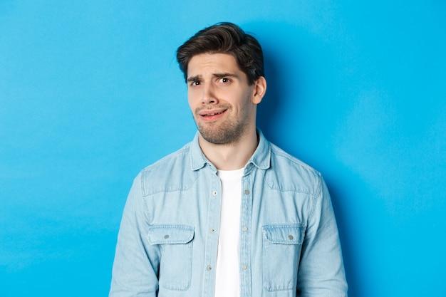 Verwarde en ongemakkelijke man die naar iets vreemds of griezeligs kijkt, ineenkrimpt van slechte advertentie, staande over de blauwe muur