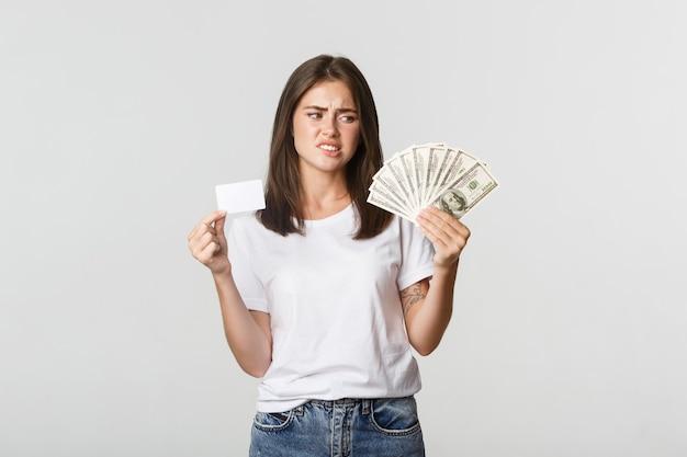 Verwarde en ontevreden jonge vrouw die naar geld kijkt en fronst, geeft de voorkeur aan creditcard.