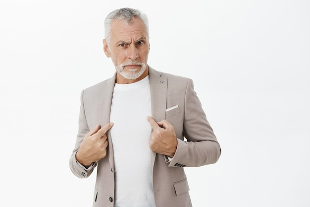 Verwarde en verdachte zakenman die op zichzelf richt