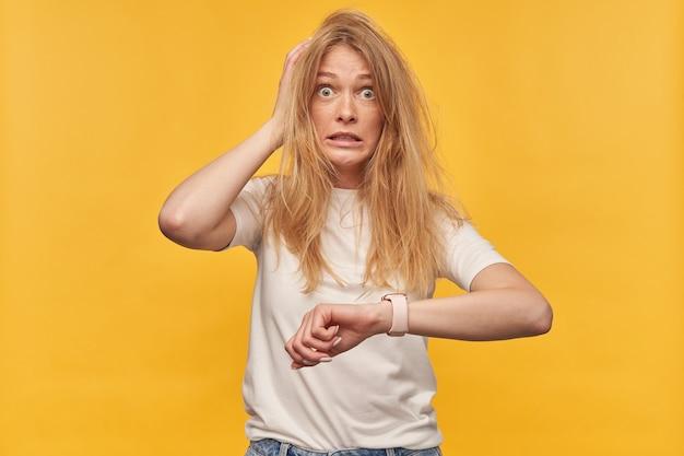Verwarde geschokte vrouw met sproeten en rommelig haar in witte t-shirt die hand met slim horloge vasthoudt en de tijd op geel controleert