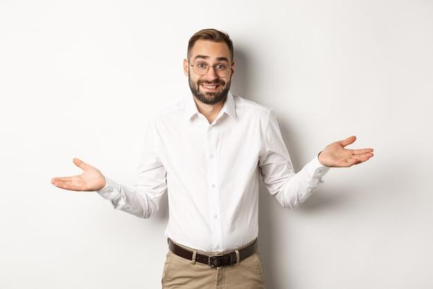 Verwarde glimlachende zakenman weet het niet, haalt zijn schouders op en zegt sorry, staande op een witte achtergrond.