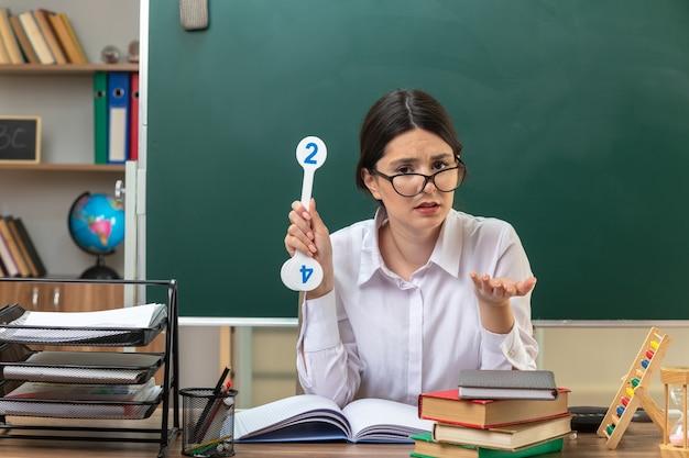 Verwarde hand uitstrekkende jonge vrouwelijke leraar met een bril die aan tafel zit met schoolgereedschap met nummerfans in de klas