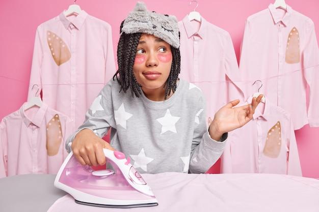 Verwarde huisvrouw strijkt overhemden van echtgenoten