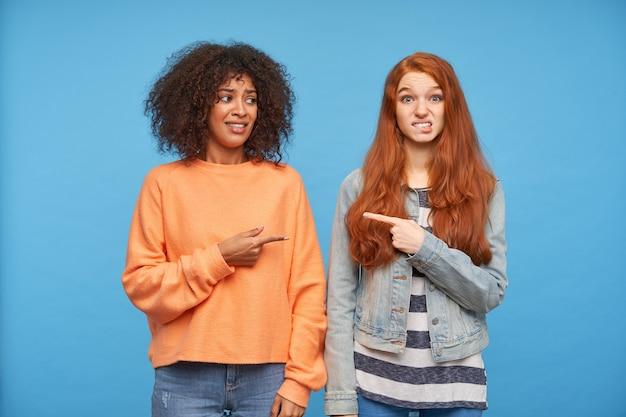 Verwarde jonge aantrekkelijke dames die elkaar tonen met opgeheven wijsvingers en fronsende wenkbrauwen met beschaamde gezichten terwijl ze over de blauwe muur staan