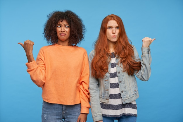 Verwarde jonge aantrekkelijke vrouwen fronsen hun wenkbrauwen met steenbolk en tonen in verschillende richtingen met opgeheven handen, geïsoleerd over blauwe muur