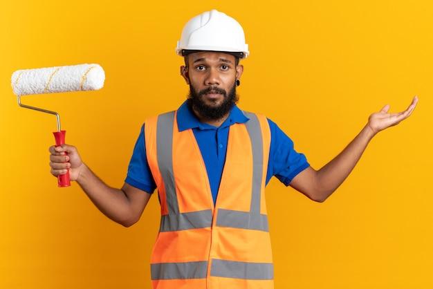 Verwarde jonge afro-amerikaanse bouwer man in uniform met veiligheidshelm verfroller te houden en zijn hand open te houden geïsoleerd op een oranje achtergrond met kopie ruimte
