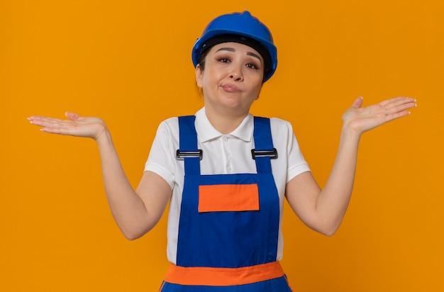 Verwarde jonge aziatische bouwersvrouw met blauwe veiligheidshelm die handen open houdt en kijkt