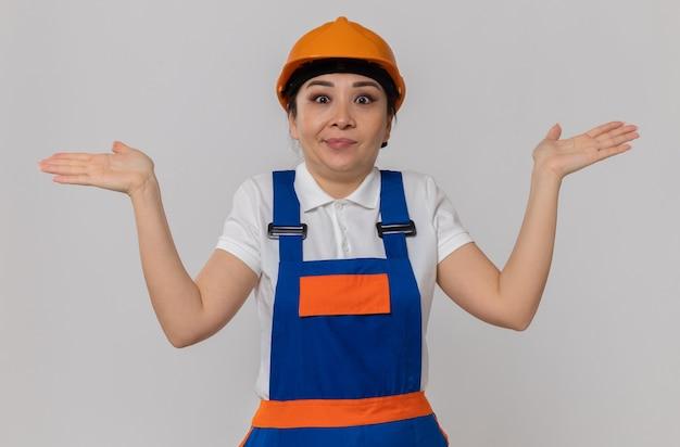 Verwarde jonge aziatische bouwersvrouw met oranje veiligheidshelm die handen open houdt