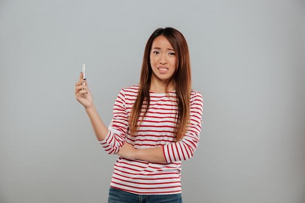Verwarde jonge aziatische dame die telefonisch spreekt