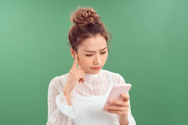Verwarde jonge aziatische vrouw die smartphone gebruikt terwijl ze over een groene achtergrond staat.