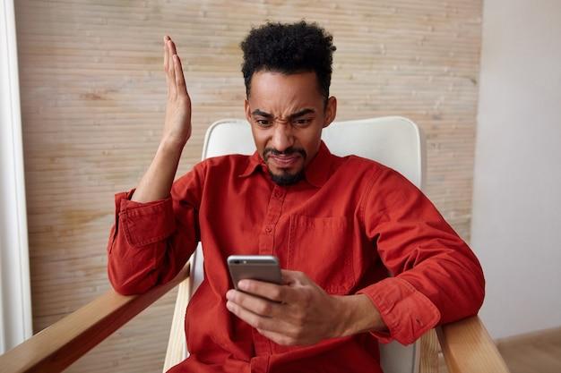 Verwarde jonge bebaarde donkere man met kort kapsel grimassen zijn gezicht en hand omhoog houden terwijl hij op zijn smartphone kijkt met steenbolk, poseren op beige