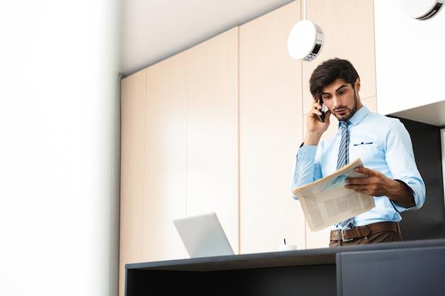Verwarde jonge bedrijfsmens bij de krant die van de keukenholding door mobiele telefoon spreekt.