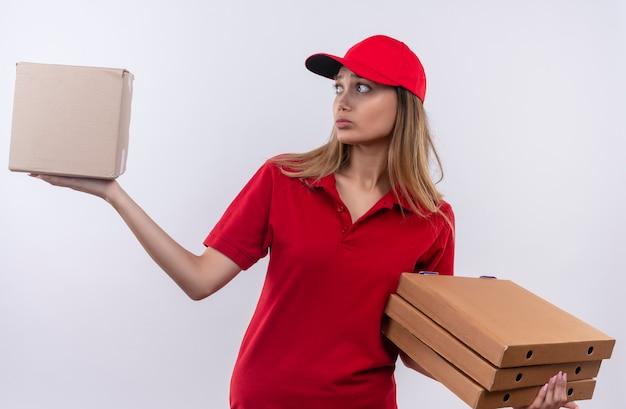 Verwarde jonge bezorger die rode uniform en pet draagt die pizzadozen houdt en doos in haar hand kijkt