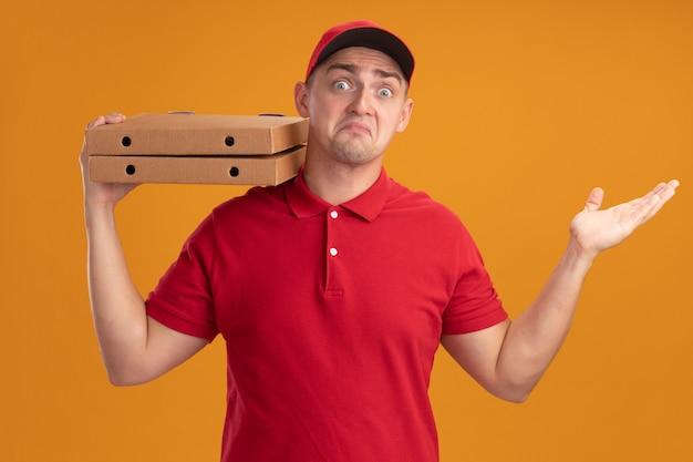 Verwarde jonge bezorger die uniform met pet draagt die pizzadozen op schouder houdt die hand verspreiden die op oranje muur wordt geïsoleerd