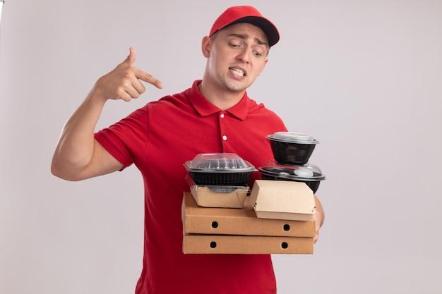 Verwarde jonge bezorger die uniform met pet draagt en wijst naar voedselcontainers op pizzadozen die op witte muur worden geïsoleerd