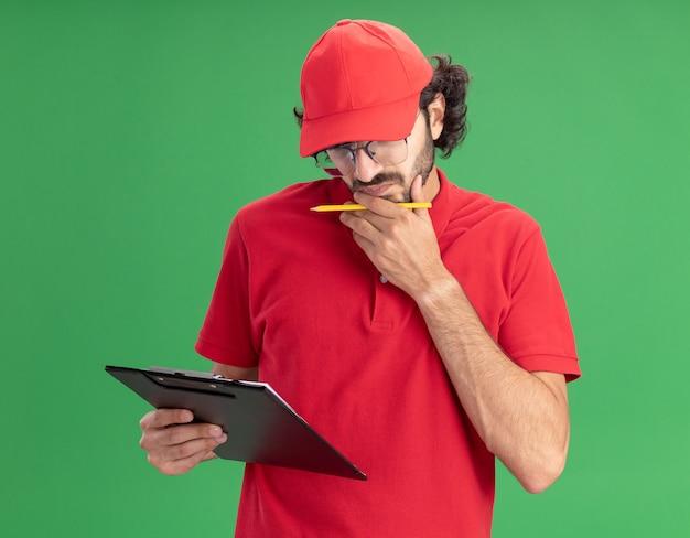 Verwarde jonge blanke bezorger in rood uniform en pet met een bril met klembord en potlood die hand op de kin zetten en naar klembord kijken dat op groene muur wordt geïsoleerd