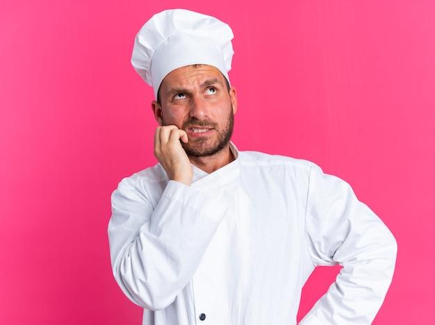 Verwarde jonge blanke mannelijke kok in uniform van de chef-kok en pet die de hand op de taille en op het gezicht houdt en omhoog kijkt geïsoleerd op roze muur