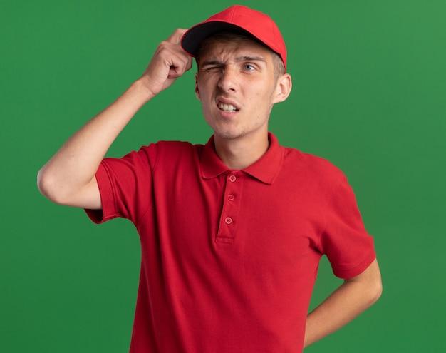 Verwarde jonge blonde bezorger legt vinger op hoofd en kijkt naar de zijkant