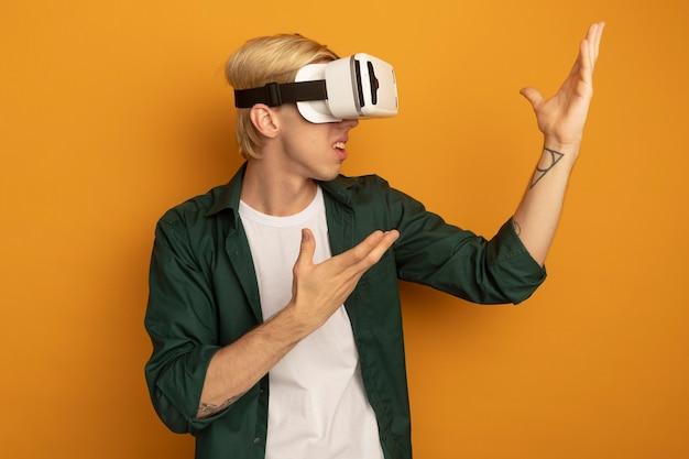 Verwarde jonge blonde kerel die groen t-shirt en vr-headset draagt, wijst met de handen aan de zijkant
