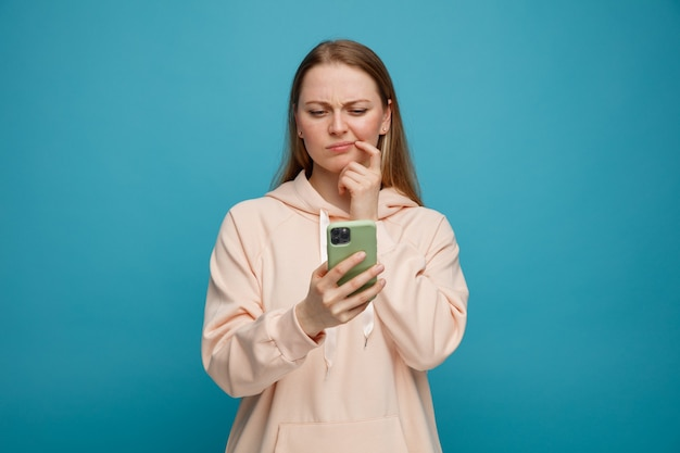 Verwarde jonge blonde vrouw aanraken van de mondhoek met vinger houden en kijken naar mobiele telefoon Gratis Foto