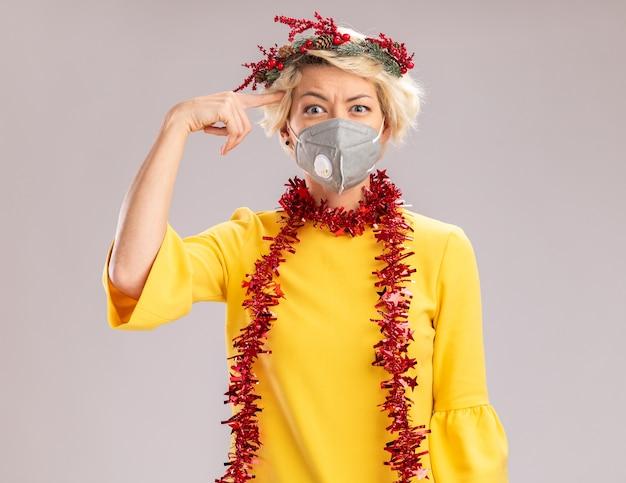 Verwarde jonge blonde vrouw die de hoofdkrans van kerstmis en klatergoudslinger om hals met beschermend masker draagt ?? die doet denk gebaar kijkt dat op witte muur wordt geïsoleerd