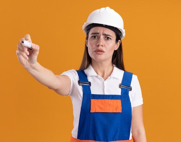 Verwarde jonge bouwersvrouw in uniform die teller standhoudt bij camera die op oranje muur wordt geïsoleerd