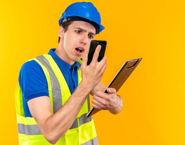 Verwarde jonge bouwman in uniform die klembord vasthoudt en naar de telefoon in zijn hand kijkt