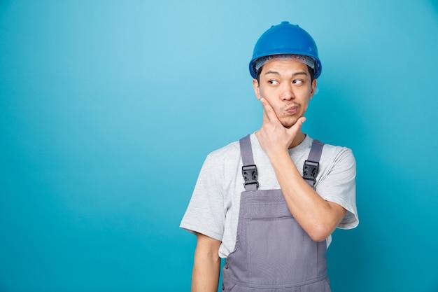 Verwarde jonge bouwvakker die veiligheidshelm en uniform draagt ?? die hand op kin houdt die kant met samengeknepen lippen bekijkt