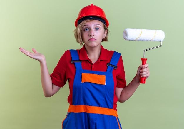 Verwarde jonge bouwvrouw in uniform met rolborstel die handen verspreidt geïsoleerd op olijfgroene muur