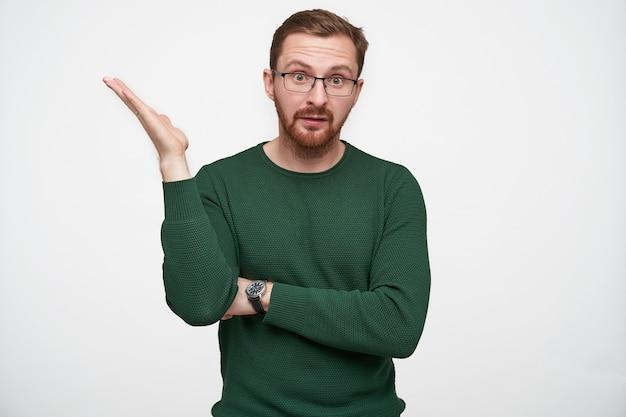 Verwarde jonge brunette man in glazen met kort kapsel emotioneel hand opheffen en voorhoofd rimpelen tijdens het kijken, geïsoleerd