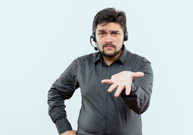 Verwarde jonge callcentermens met hoofdtelefoon die hand naar camera stak