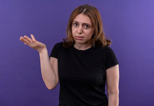 Verwarde jonge casual vrouw met lege hand op geïsoleerde paarse ruimte