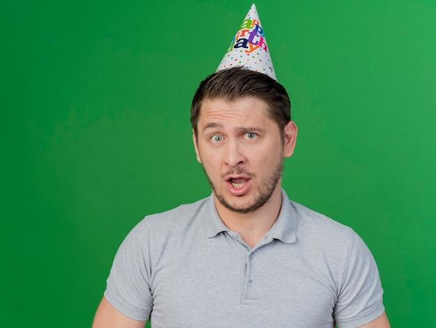 Verwarde jonge feest man met verjaardag pet geïsoleerd op groen