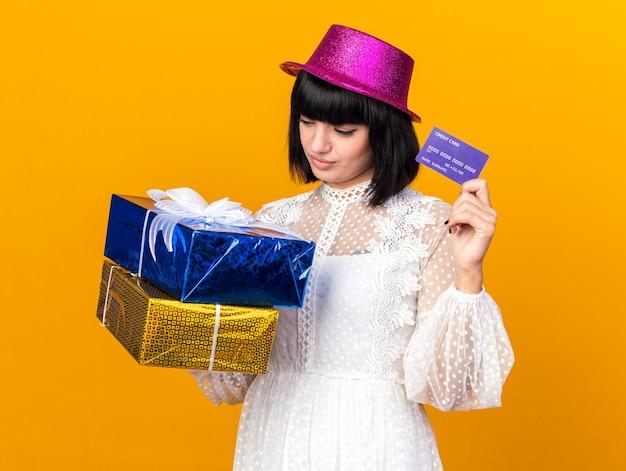 Verwarde jonge feestvrouw met een feesthoed met cadeaupakketten en creditcard die naar pakketten kijkt die op een oranje muur zijn geïsoleerd