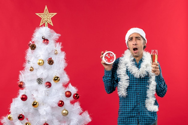 Verwarde jonge kerel met kerstman hoed en met een glas wijn en klok staande in de buurt van de kerstboom