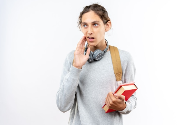 Verwarde jonge kerelstudent die rugzak met hoofdtelefoons op hals draagt die boeken houden die op witte muur worden geïsoleerd