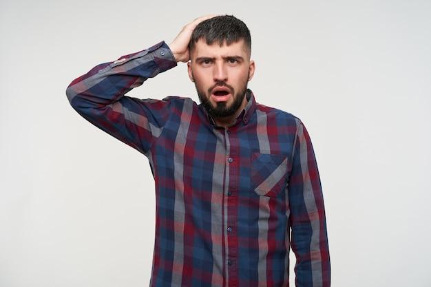 Verwarde jonge knappe donkerharige, bebaarde man met kort kapsel die perplex kijkt en opgeheven hand op zijn hoofd houdt, staande over een witte muur