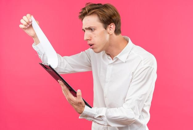Verwarde jonge knappe kerel die een wit overhemd draagt dat klembord vasthoudt en bekijkt?
